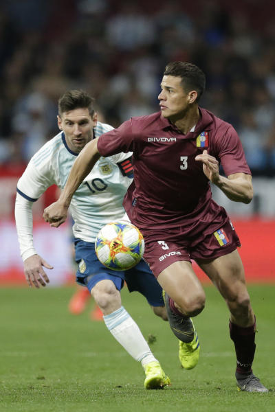 Argentina's Lionel Messi, left, fights for the ball with Venezuela's Yordan Osorio during an international friendly soccer match between Argentina and Venezuela at Wanda Metropolitano stadium in Madrid, Spain, Friday, March 22, 2019. (AP Photo/Bernat Armangue)