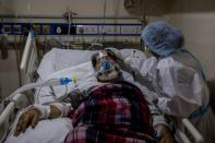 A medical worker tends to a patient suffering from COVID-19, inside the ICU ward at Holy Family Hospital in New Delhi