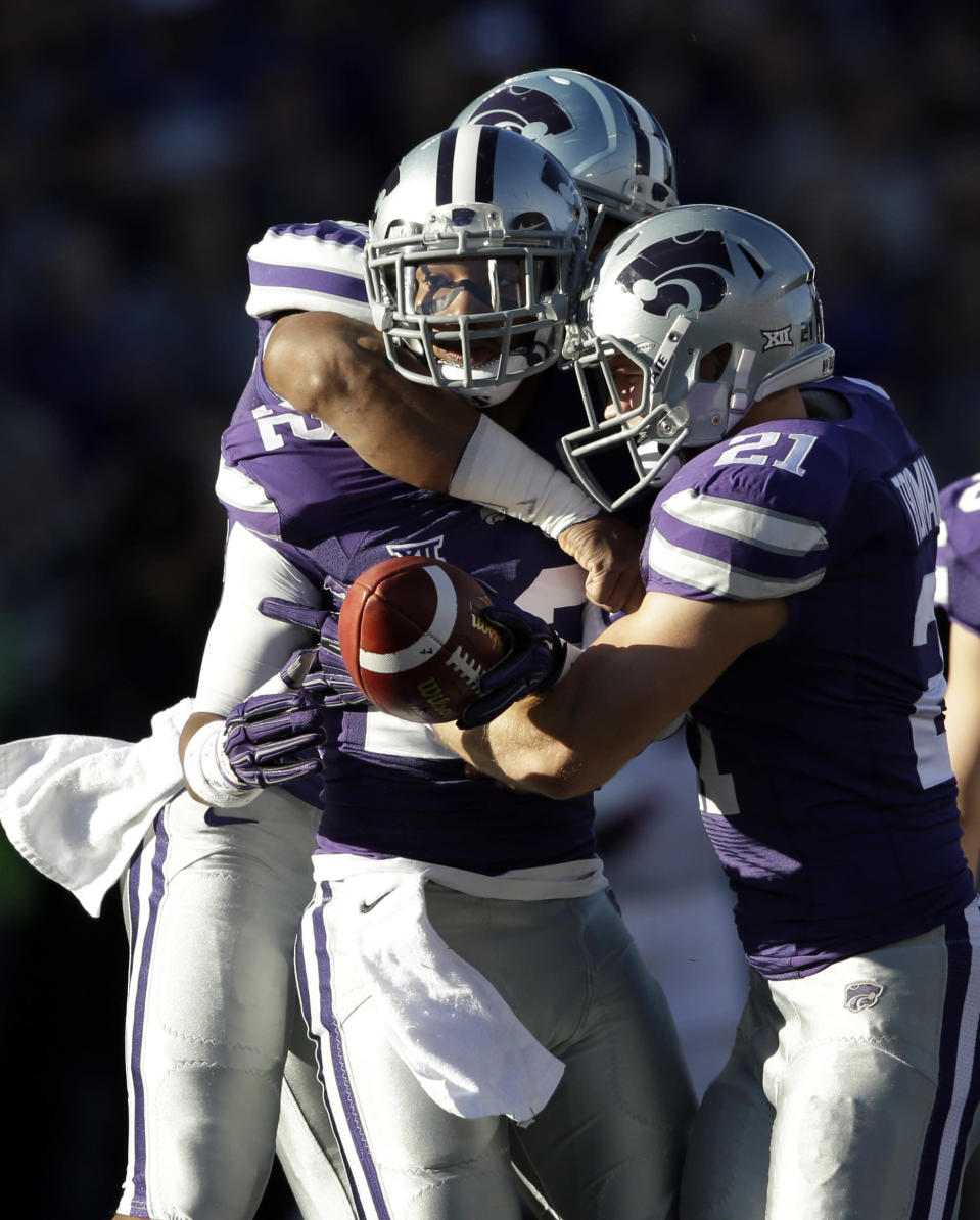 Kansas State defensive back Dante Barnett (22) is congratulated by teammates including Kansas State linebacker Jonathan Truman (21) following an interception during the first half of an NCAA college football game against Kansas in Manhattan, Kan., Saturday, Nov. 29, 2014. (AP Photo/Orlin Wagner)