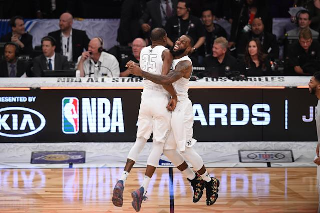 """<a class=""""link rapid-noclick-resp"""" href=""""/nba/players/3704/"""" data-ylk=""""slk:LeBron James"""">LeBron James</a> and <a class=""""link rapid-noclick-resp"""" href=""""/nba/players/4244/"""" data-ylk=""""slk:Kevin Durant"""">Kevin Durant</a> embrace during the 2018 NBA All-Star Game, probably because they just remembered all those flaming hot bars they spit in the summer of 2011. (AFP)"""