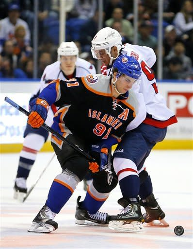New York Islanders center John Tavares (91) battles for the puck with Washington Capitals center Mike Ribeiro (9) during the first period of an NHL hockey game at the Nassau Coliseum in Uniondale, N.Y., Saturday, March 9, 2013. (AP Photo/Paul J. Bereswill)