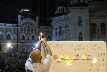 A man places a candle on top of a white board set up to place messages for passengers onboard the missing Malaysia Airlines Flight MH370 during a candlelight vigil in Kuala Lumpur