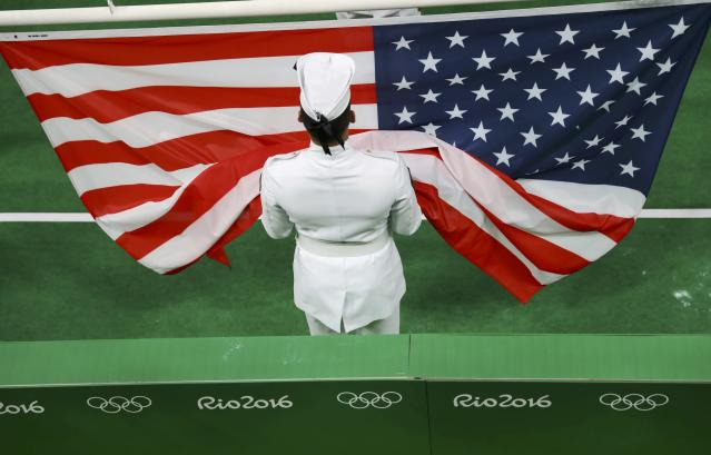 2016 Rio Olympics - Artistic Gymnastics - Victory Ceremony - Women's Individual All-Around Victory Ceremony - Rio Olympic Arena - Rio de Janeiro, Brazil - 11/08/2016. The U.S. flag is unfurled for the victory ceremony after Simone Biles (USA) of USA and Alexandra Raisman (USA) of USA (Aly Raisman) won gold and silver respectively in the women's individual all-around final. REUTERS/Kai Pfaffenbach FOR EDITORIAL USE ONLY. NOT FOR SALE FOR MARKETING OR ADVERTISING CAMPAIGNS.