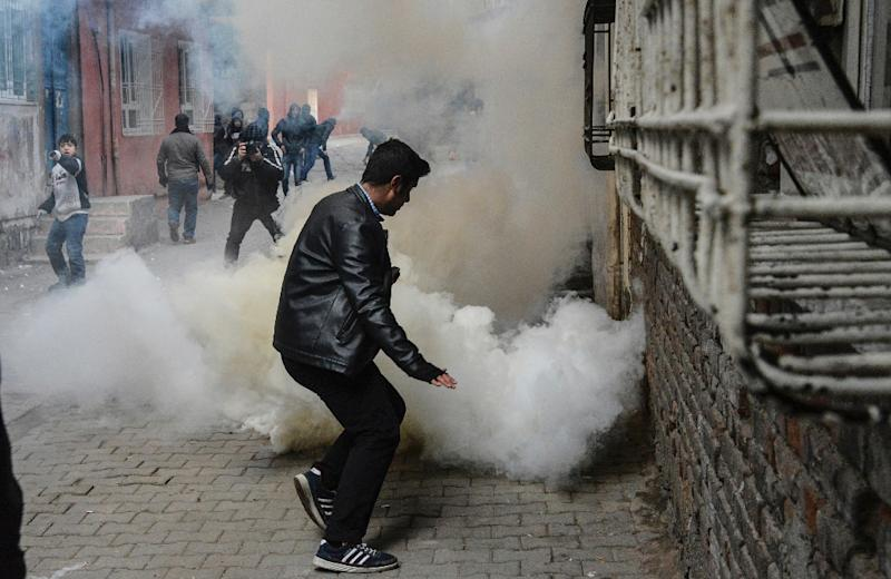 A man takes evasive action as a tear gas canister explodes during clashes with police in the Sur district of Diyarbakir, southeastern Turkey, on January 3, 2016 (AFP Photo/Ilyas Akengin)