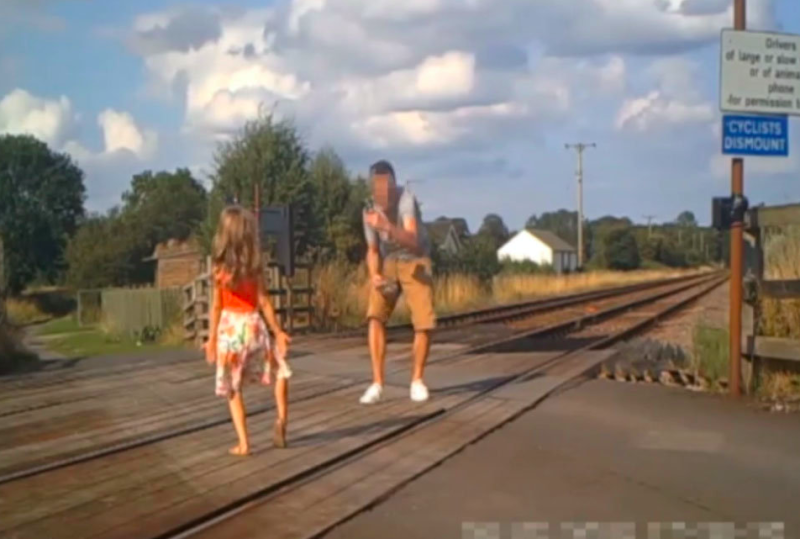 A father can be seen taking pictures of a little girl in different directions on the level crossing. (SWNS)