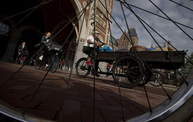 Bicycles pass through Rijksmuseum, in Amsterdam, Netherlands, Monday May 13, 2013, signaling the end of more than a decade of efforts by cyclists to ensure a passageway that runs under and through the Rijksmuseum would remain open to bike traffic. The museum, which houses masterpieces by Rembrandt van Rijn and Vincent van Gogh, among others, opened last month after a 10-year renovation. Architects and successive museum directors had opposed allowing bikes through, and a local government tried to have them barred on safety grounds. But in a city that has more bicycles than people, the bike lobby prevailed. (AP Photo/Peter Dejong)