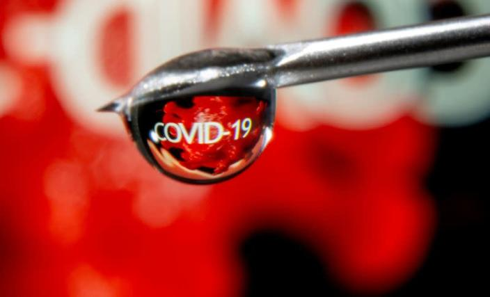 """FILE PHOTO: FILE PHOTO: The word """"COVID-19"""" is reflected in a drop on a syringe needle in this illustration"""