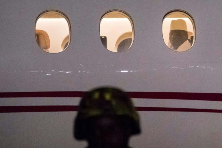 Gone: Jammeh looks through the window of a plane at Banjul airport as he prepares to leave The Gambia on January 21 2017 (AFP/STRINGER)