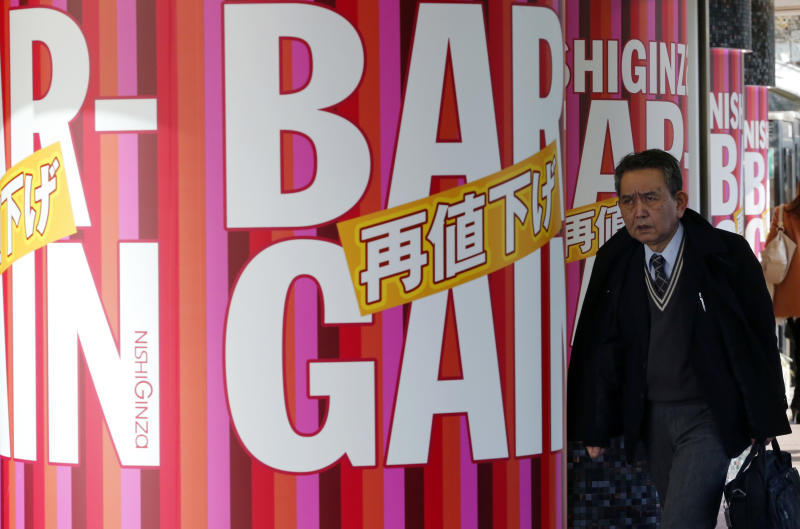 In this Jan. 28, 2014 photo, a man walks by a shopping mall pillars decorated with bargain sale advertisements, offering further price reduction, in Tokyo. Japan's consumer price index rose 0.4 percent in 2013, the first increase in five years, in further evidence the recovery in the world's third-largest economy is gaining momentum. (AP Photo/Shizuo Kambayashi)