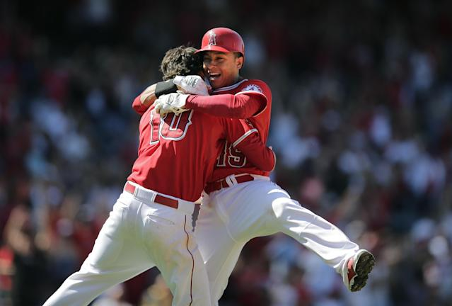 Los Angeles Angels' Grant Green, left, celebrates his ninth-inning walk-off single with Efren Navarro after a baseball game against the Seattle Mariners on Sunday, July 20, 2014, in Anaheim, Calif. The Angles won 6-5. (AP Photo/Jae C. Hong)