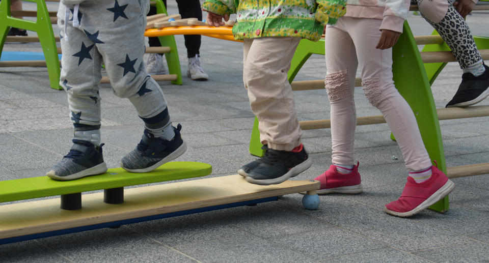 Kids in colourful outfits play in a playground.