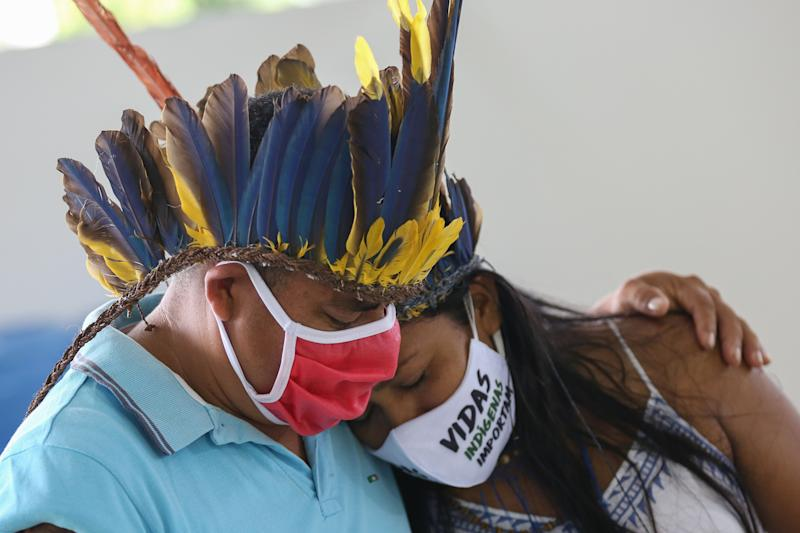 TOPSHOT - Indigenous people from the Parque das Tribos community mourn at the funeral of chief Messias, 53, of the Kokama tribe, who died from the new coronavirus, COVID-19, in Manaus, Brazil, on May 14, 2020. (Photo by MICHAEL DANTAS / AFP) (Photo by MICHAEL DANTAS/AFP via Getty Images)