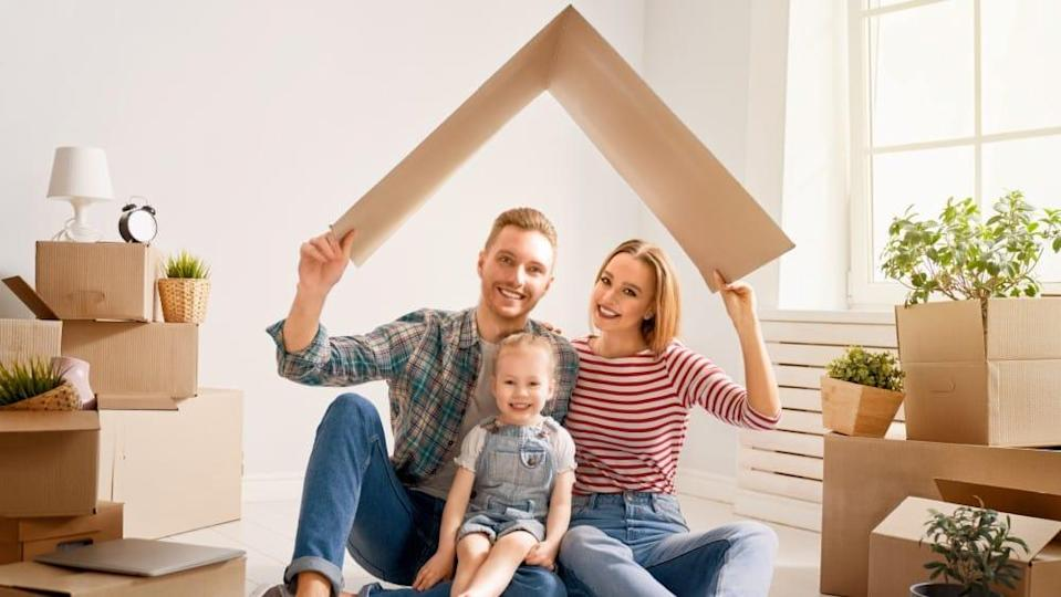 Mother, father and child girl in new house with a cardbox roof. Symbol of protection and property.