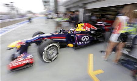 Red Bull Formula One driver Sebastian Vettel of Germany drives out of the team garage during the first practice session of the Singapore F1 Grand Prix at the Marina Bay street circuit in Singapore September 20, 2013. REUTERS/Pablo Sanchez