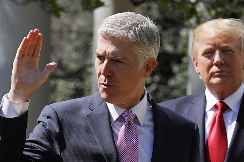 U.S. Supreme Court Associate Justice Judge Neil Gorsuch takes the judicial oath as President Donald Trump looks on: Chip Somodevilla/Getty Images