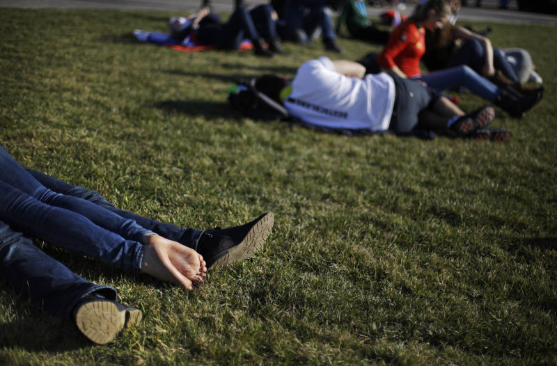 A couple at left, lie on the lawn under the Olympic cauldron at the 2014 Winter Olympics, Wednesday, Feb. 12, 2014, in Sochi, Russia. Temperatures are predicted near 60 degrees Fahrenheit in Sochi on Wednesday. (AP Photo/David Goldman)