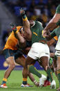 Australia's Tom Banks, center, is lifted in a tackle by South Africa's Siya Kolisi, right, during their Rugby Championship match on Sunday, Sept. 12, 2021, Gold Coast, Australia. (AP Photo/Tertius Pickard)