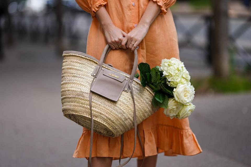 PARIS, FRANCE - MAY 10: Ketevan Giorgadze @katie.one wears a long buttoned coral loungewear linen The Sleeper dress with puffy sleeves, gold rings, a wicker with brown shiny leather detail Le Panier Soleil Jacquemus tote-bag, on May 10, 2021 in Paris, France. (Photo by Edward Berthelot/Getty Images)