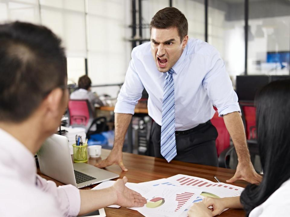 bad-tempered caucasian business executive yelling at two asian subordinates in office