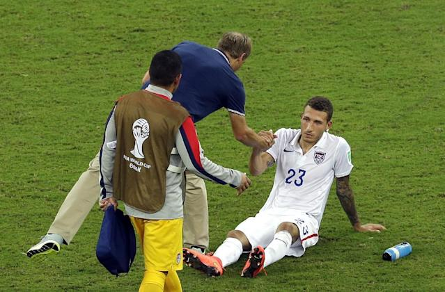 United States' Fabian Johnson, right, shakes hand with head coach Juergen Klinsmann after a 2-2 draw in the group G World Cup soccer match between the USA and Portugal at the Arena da Amazonia in Manaus, Brazil, Sunday, June 22, 2014. (AP Photo/Themba Hadebe)