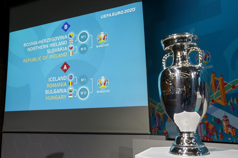 The match fixtures are shown on an electronic panel next to the Henri Delaunay trophy after the drawing of the UEFA EURO 2020 Play-off matches at the UEFA headquarters in Nyon, Switzerland, Friday, Nov. 22, 2019. (Salvatore Di Nolfi/Keystone via AP)