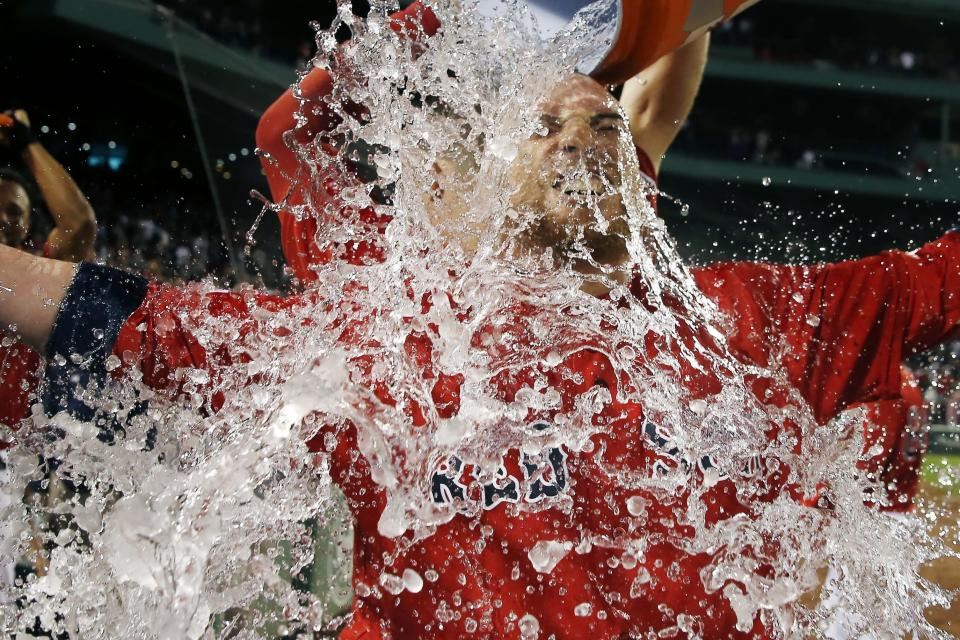 A teammate douses Boston Red Sox's Christian Vazquez after his walkoff home run during the 10th inning of a baseball game against the Toronto Blue Jays in Boston, Friday, June 21, 2019. (AP Photo/Michael Dwyer)