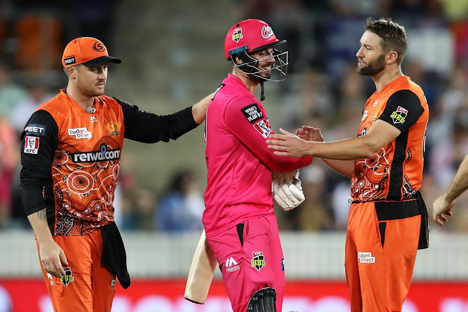 James Vince of the Sixers shows his frustration as he shakes hands with Andrew Tye of the Scorchers after Tye bowled wide that gave the Sixers the win and left Vince not out on 98.