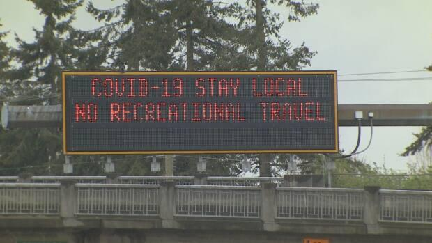 An electronic sign on a highway in Metro Vancouver reminding residents to keep to their local areas under new non-essential travel restrictions meant to slow COVID-19 infections. (Doug Kerr/CBC News - image credit)