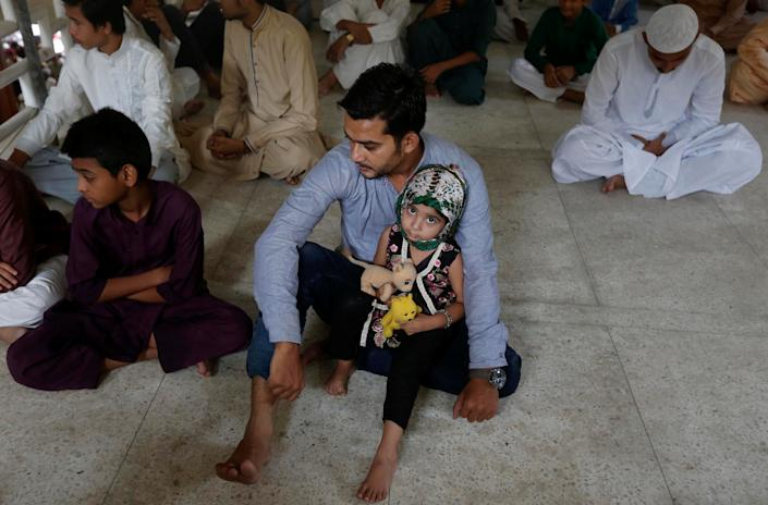 A girl holds her stuffed toys as she sits with her father as they listen to sermon with others before Friday prayers at a mosque during a Muslim holy month of Ramadan in Karachi, Pakistan June 16, 2017. REUTERS/Akhtar Soomro