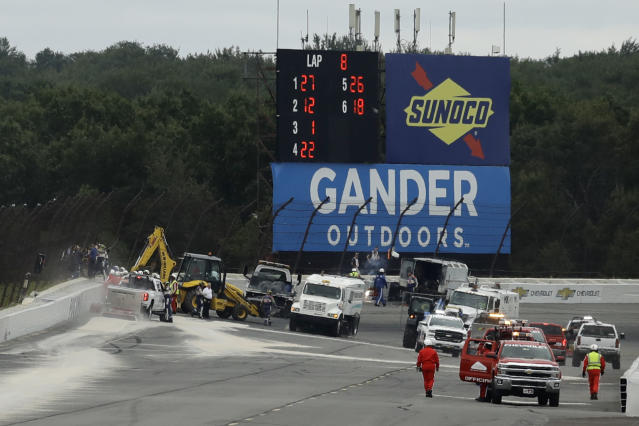 Track workers repair a section of fence after a wreck during the IndyCar auto race at Pocono Raceway, Sunday, Aug. 19, 2018, in Long Pond, Pa. (AP Photo/Matt Slocum)