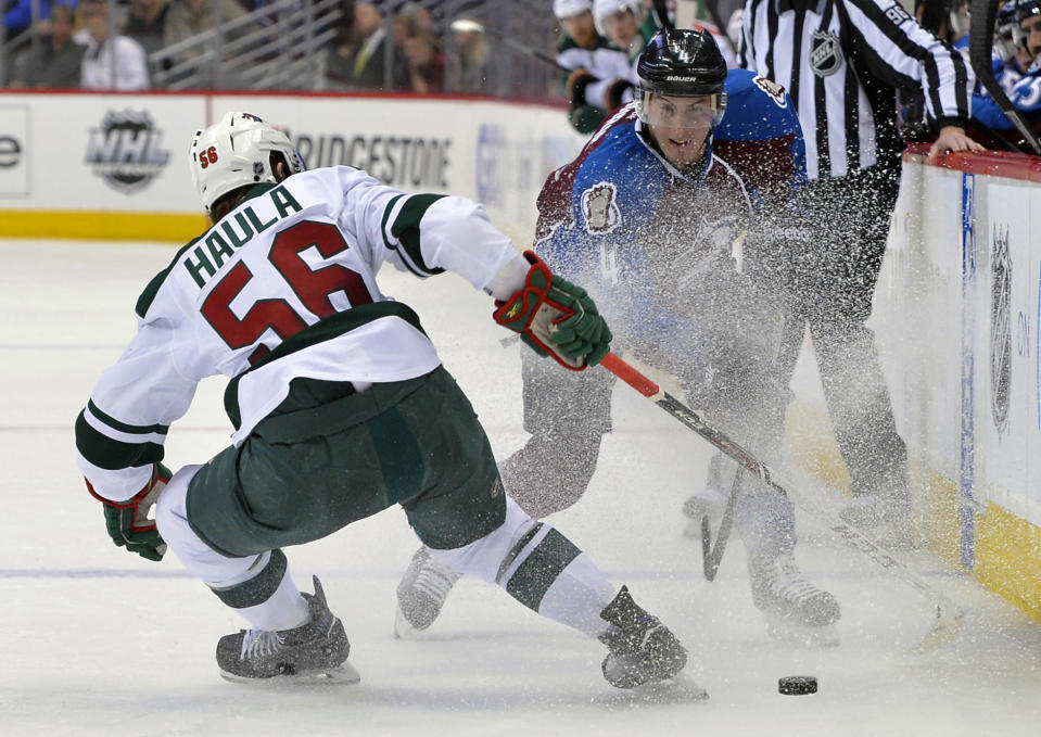 Colorado Avalanche defenseman Tyson Barrie (4) and Minnesota Wild left wing Erik Haula (56), from Finland, skate in a spray of ice during the second period in Game 1 of an NHL hockey first-round playoff series on Thursday, April 17, 2014, in Denver. (AP Photo/Jack Dempsey)