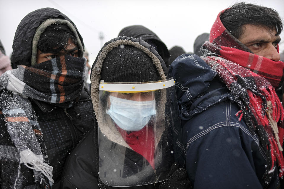 Migrants, one wearing protective equipment against the new coronavirus, wait to be relocated during a snowfall at the Lipa camp northwestern Bosnia, near the border with Croatia, Saturday, Dec. 26, 2020. Hundreds of migrants are stranded in a burnt-out squalid camp in Bosnia as heavy snow fell in the country and temperatures dropped during a winter spell of bad weather after fire earlier this week destroyed much of the camp near the town of Bihac that already was harshly criticized by international officials and aid groups as inadequate for housing refugees and migrants.(AP Photo/Kemal Softic)