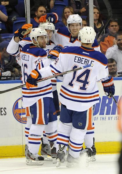 Edmonton Oilers' Taylor Hall (4), Mark Arcobello (26), Jeff Petry (2) and Jordan Eberle (14) celebrate Hall's second goal in the first period of an NHL hockey game on Thursday, Oct. 17, 2013, in Uniondale, N.Y. (AP Photo/Kathy Kmonicek)