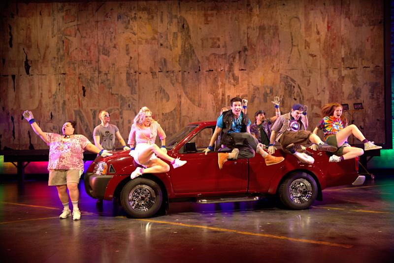 """This theater image released by The Hartman Group shows the cast during a performance of """"Hands on a Hard Body,"""" at the Brooks Atkinson Theater in New York and featuring songs co-written by Phish frontman Trey Anastasio. (AP Photo/The Hartman Group, Chad Batka)"""