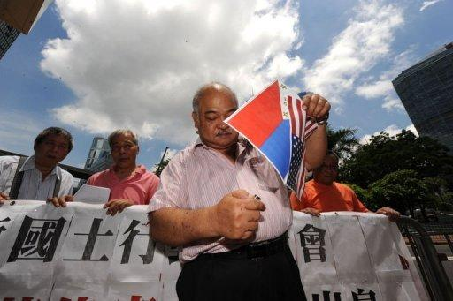 Protester Tsang Kin-shing, who supports Chinese sovereignty over the Scarborough Shoal, prepares to burn paper Philippine and a US flags outside the Philippine consulate in Hong Kong. China has told its citizens they were not safe in the Philippines and its state media warned of war, as a month-long row over rival claims in the South China Sea threatened to spill out of control