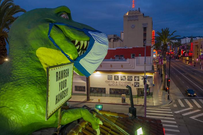 The dinosaur atop the Ripley's Believe It or Not! Odditorium wears a mask to encourage people to take safety measures as coronavirus infections spread on April 19, 2020.