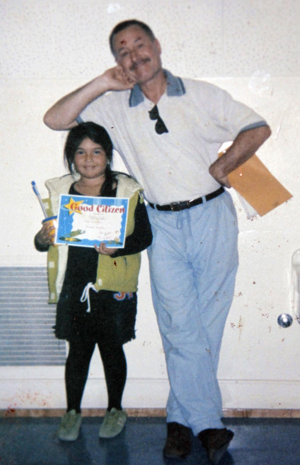EDS: THIS CORRECTS SOURCE'S LAST NAME - This 2003 photo provided by Flor Cervantes shows former Miramontes Elementary teacher Mark Berndt with her sister, Angelica Zuniga, holding a citizenship diploma given to her by Brendt, at the school in Los Angeles. Angelica Zuniga, 16, now a high school junior, said Berndt, who is suspected of taking bondage-style photographs of children in his class, never asked her or others to do anything strange or to play any inappropriate games. (AP Photo/Flor Cervantes)