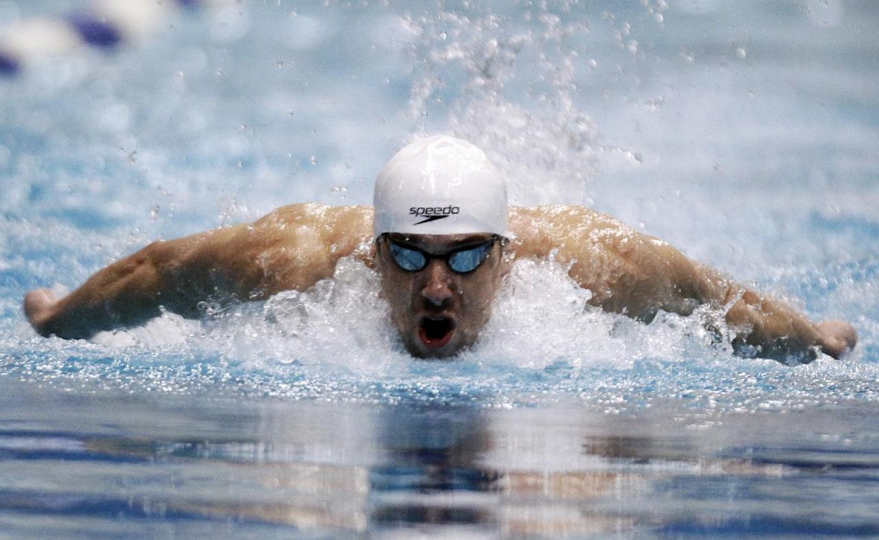 Michael Phelps competes in the 100-meter butterfly at the Indianapolis Grand Prix swimming meet in Indianapolis, Thursday, March 29, 2012. (AP Photo/Michael Conroy)