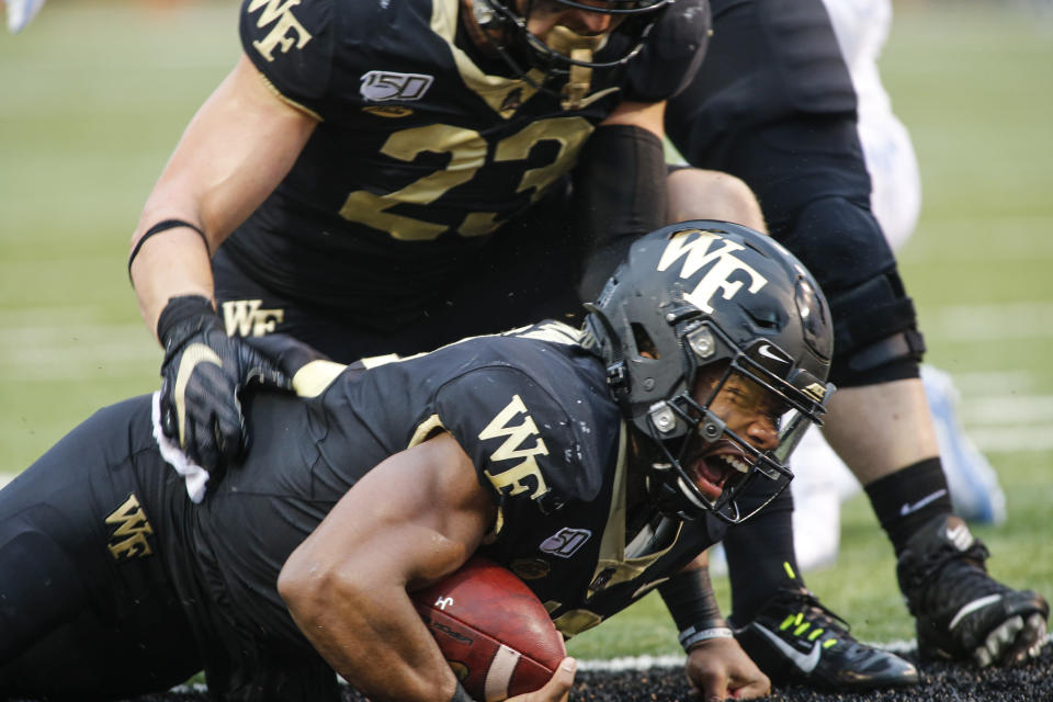 Wake Forest quarterback Jamie Newman, bottom, yells as he is helped up by tight end Brandon Chapman after Newman scored his second touchdown against North Carolina, during the first half of an NCAA college football game in Winston-Salem, N.C., Friday, Sept. 13, 2019. (AP Photo/Nell Redmond)