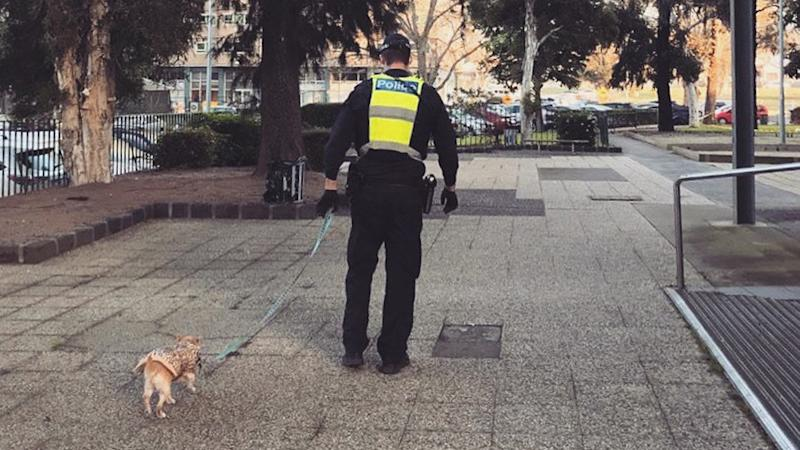 A police officer walks a dog for a resident in one of the Melbourne towers.