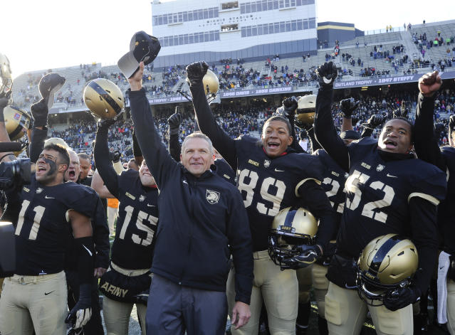Army head coach Jeff Monken, center, celebrates a 21-16 win against Duke after singing the West Point alma mater with his players and cadets after an NCAA college football game on Saturday, Nov. 11, 2017, in West Point, N.Y. (AP Photo/Hans Pennink)
