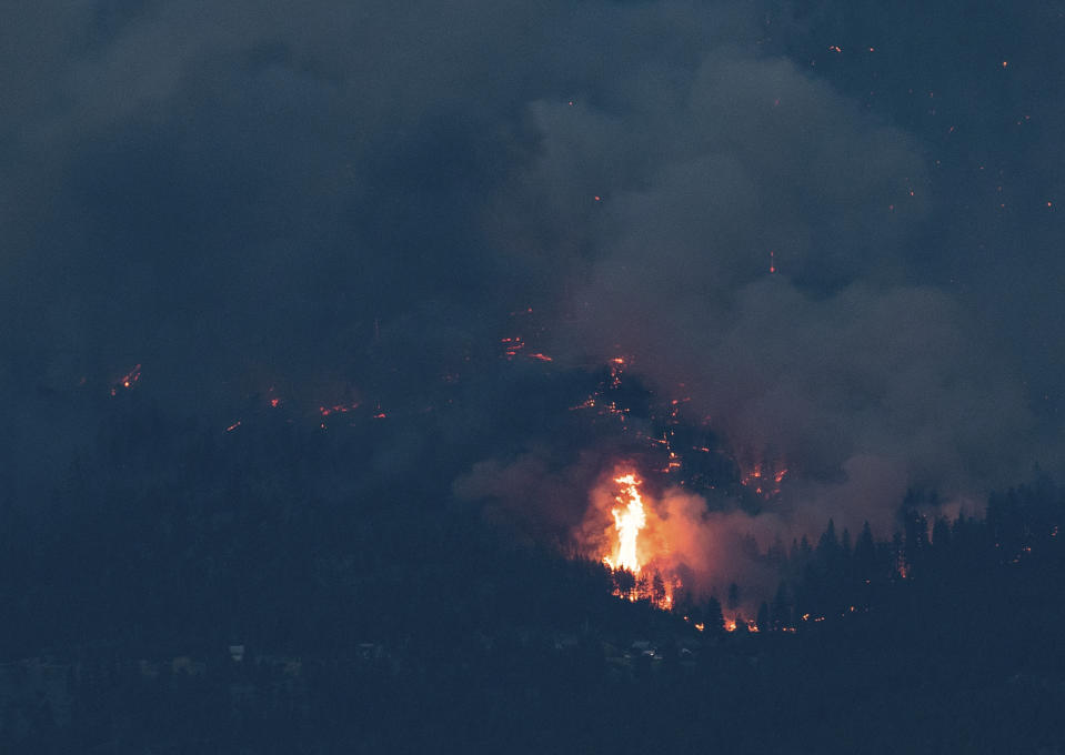 Flames leap into the air as a wider wildfire burns on the side of a mountain in Lytton, B.C., at dusk on Thursday, July 1, 2021. (Darryl Dyck/The Canadian Press via AP)