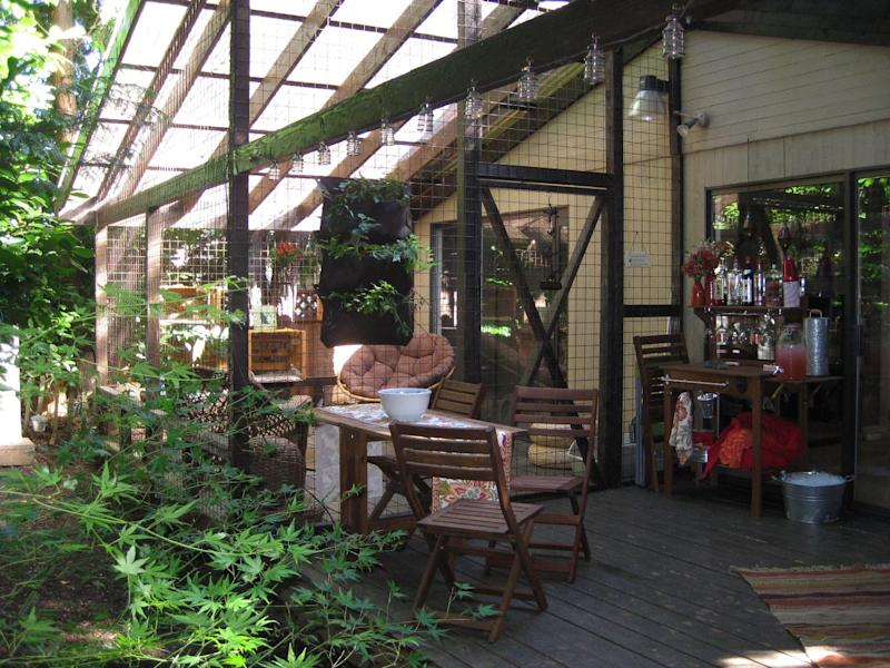 This undated photo provided by Carrie Fagerstrom shows Fagerstrom's catio at her home in Portland, Ore. The playground designed for her eight cats is a covered, enclosed patio attached to her house that includes scratching posts, a small water fountain and plenty of cat toys. She spent $5,000 on the catio, which allows her cats to be exposed to fresh air and scenery, but keeps them safe from harmful outdoor elements. (AP Photo, Carrie Fagerstrom)