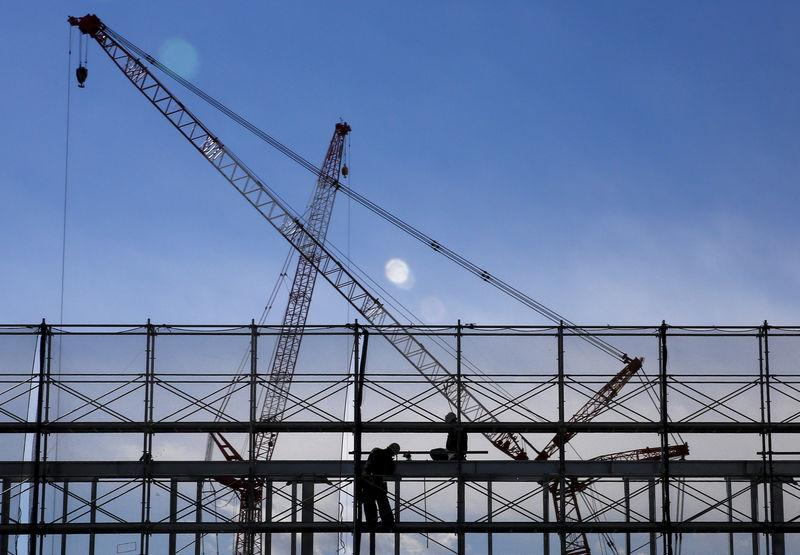 File picture of men working on a scaffolding as cranes are silhouetted against the sky at a construction site in Tokyo