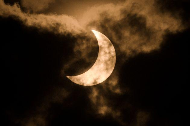 The partial solar eclipse is captured using infra red filter in the cloudy sky in Nairobi, Kenya on June 21, 2020.