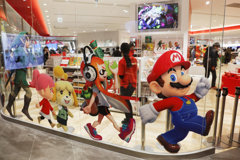 FILE - In this Jan. 23, 2020, file photo, Nintendo characters, including Mario, right, are seen on a glass of its official store in Tokyo. Nintendo Co.'s profit for the fiscal year ended in March jumped 86% on healthy sales of the Switch handheld machine as people staying at home over the pandemic turned to video games. (AP Photo/Jae C. Hong, File)