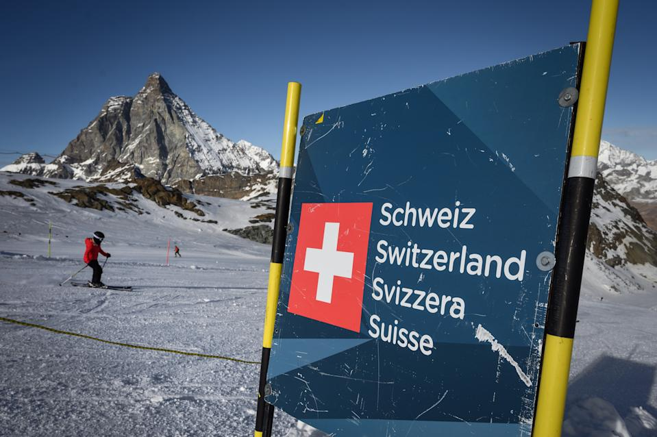 A skier hits the slopes past a banner showing Swiss border above the ski resort of Zermatt in the Swiss Alps on November 28, 2020. - As EU countries debate a bloc-wide ban on ski holidays to curb coronavirus infections, downhill enthusiasts may be tempted to head to non-member Switzerland, where the winter season is well underway. (Photo by Fabrice COFFRINI / AFP) (Photo by FABRICE COFFRINI/AFP via Getty Images)