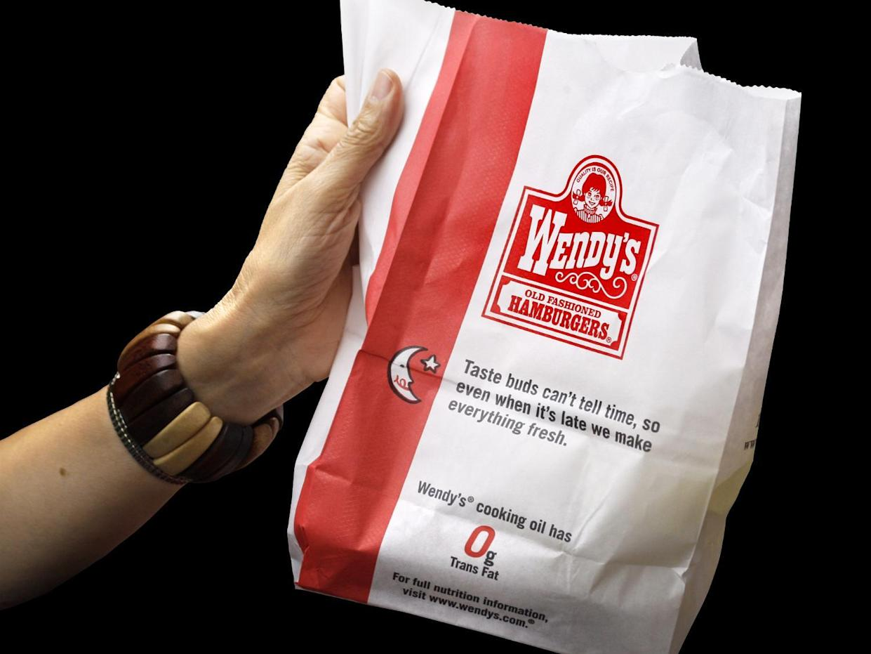 Hand holding bag of Wendy's fast food, graphic element on black