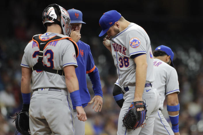 New York Mets' Tylor Megill (38) talks with pitching coach Jeremy Hefner, second from left, and teammates during the fourth inning of a baseball game against the Milwaukee Brewers, Friday, Sept. 24, 2021, in Milwaukee. (AP Photo/Aaron Gash)