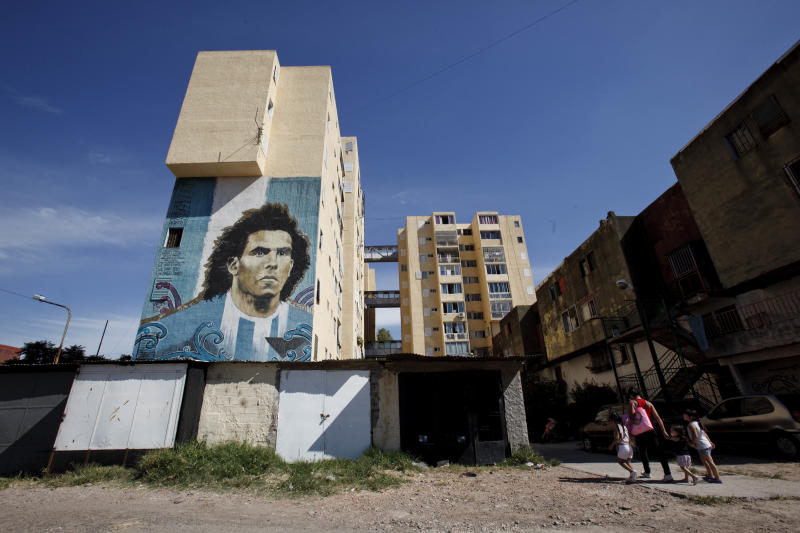 """In this March 8, 2013 photo, a mural of soccer star Carlos Tevez by artists Martin Ron, Lean Frizzera and Emy Mariani covers the Fuerte Apache apartment complex where Tevez grew up in Buenos Aires, Argentina, Friday, March 8, 2013 . The painting of Tevez is part of a project titled """"Sanctification of popular idols."""" Artist Martin Ron said they painted Tevez on the building where the idol was born and grew up, which is also near a soccer field, to inspire youth who play there. (AP Photo/Natacha Pisarenko)"""